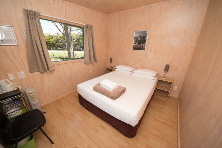 Small and comfortable cabins with Queen bed, sharing communal holiday park facilities.